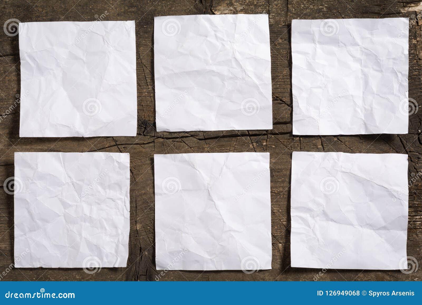 Seis amarrotaram papéis de nota brancos vazios na superfície de madeira