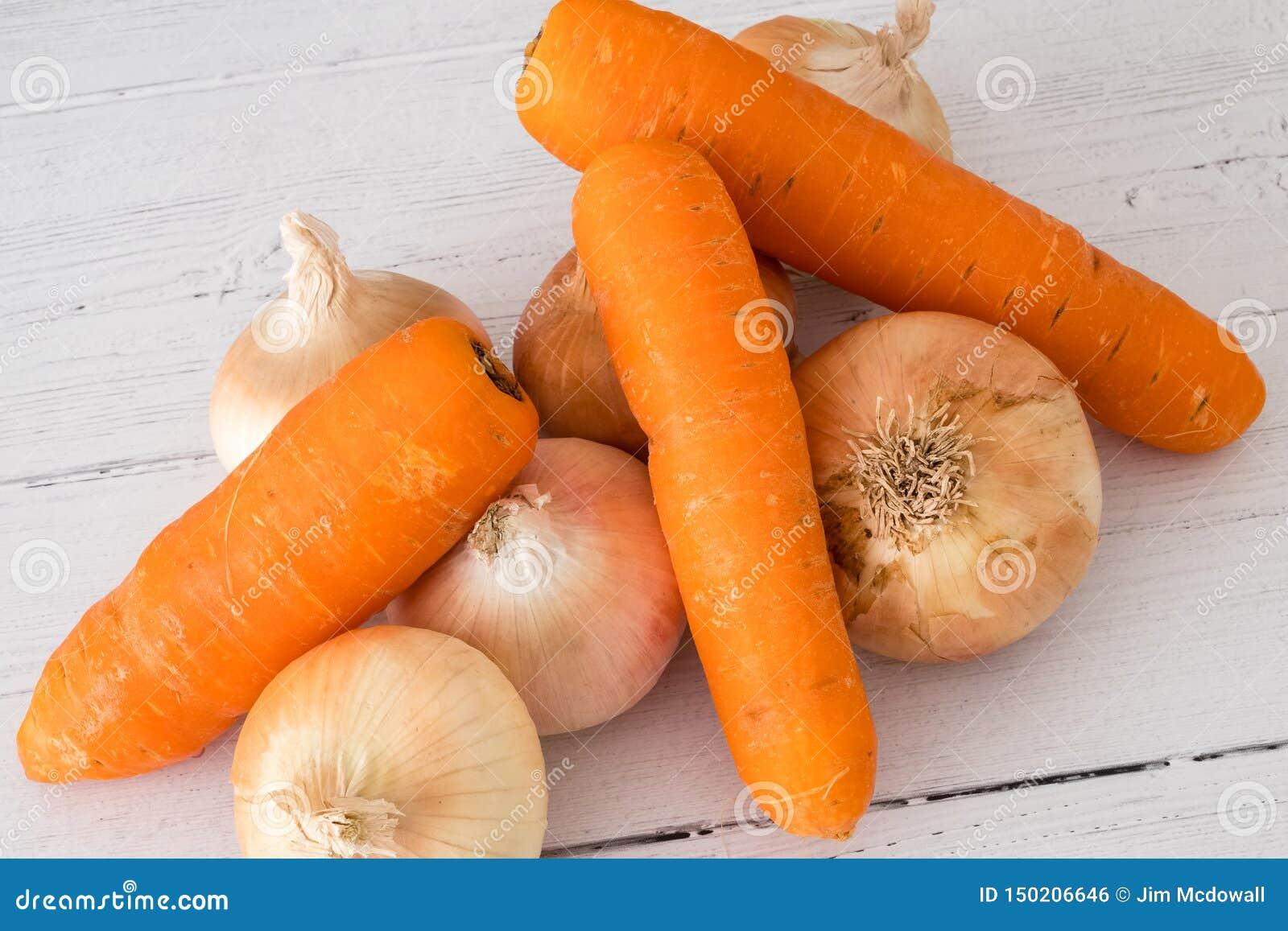 Seis cebollas producidas escocesas de oro y tres zanahorias una de sus cinco un día en la consumición sana