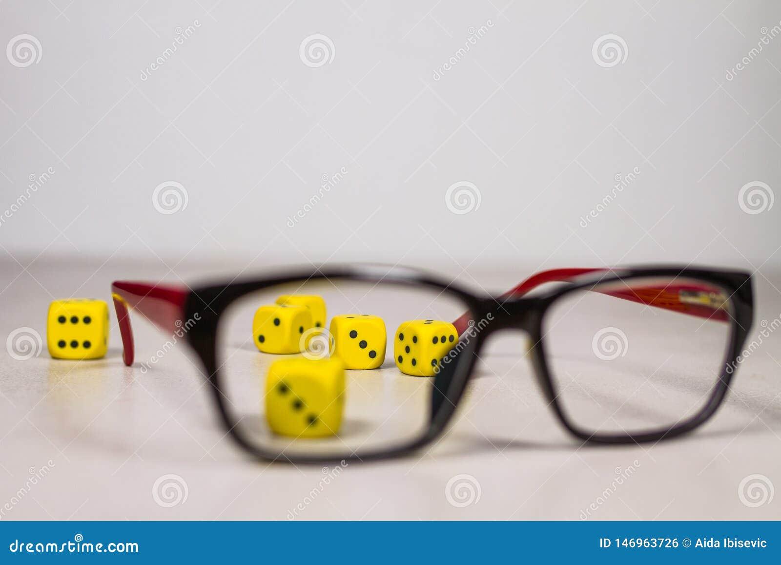 Seis dados amarillos en Gray White Background Behind Glasses limpio