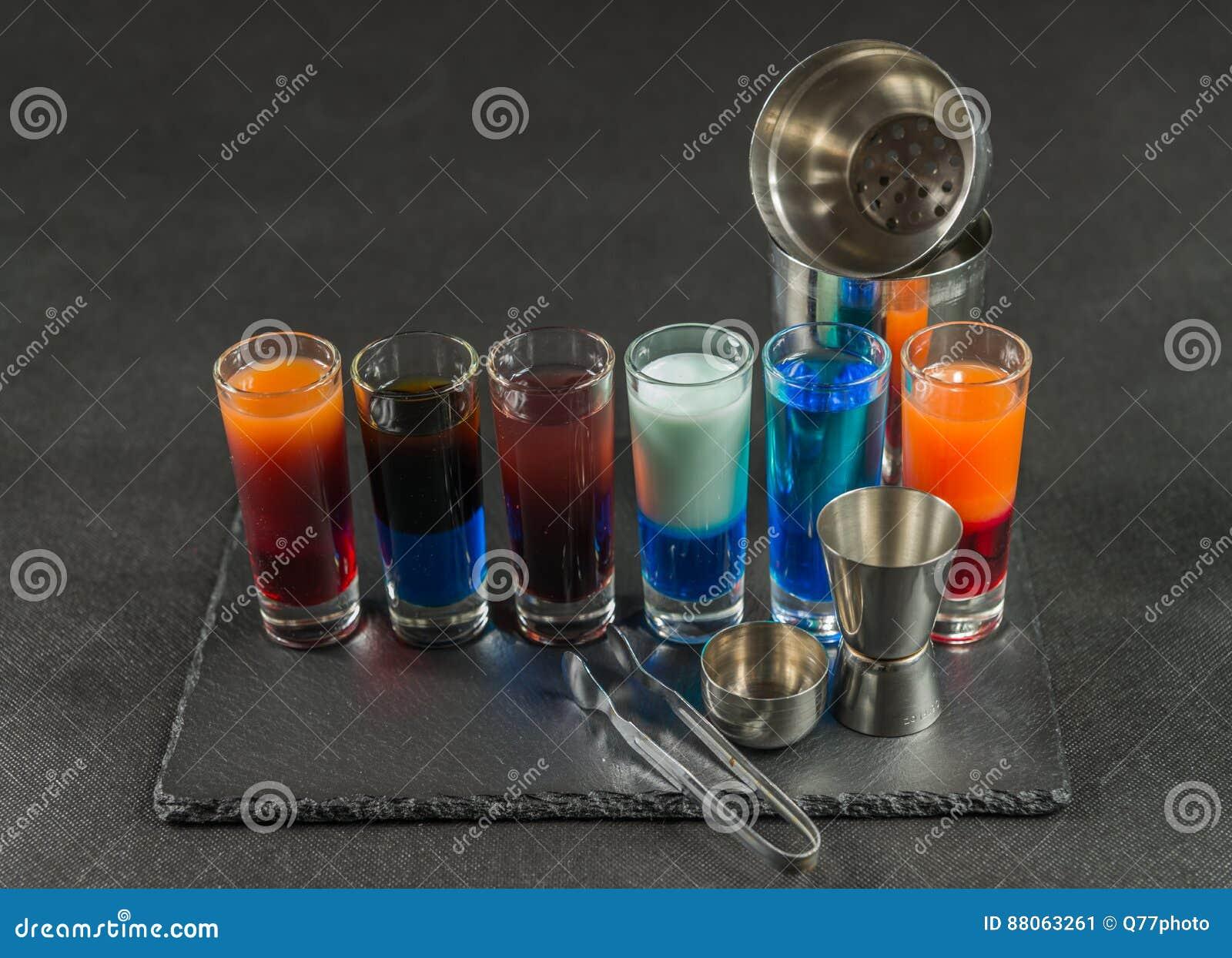 Seis diversas bebidas coloreadas del tiro, alineadas en un pla negro de la piedra