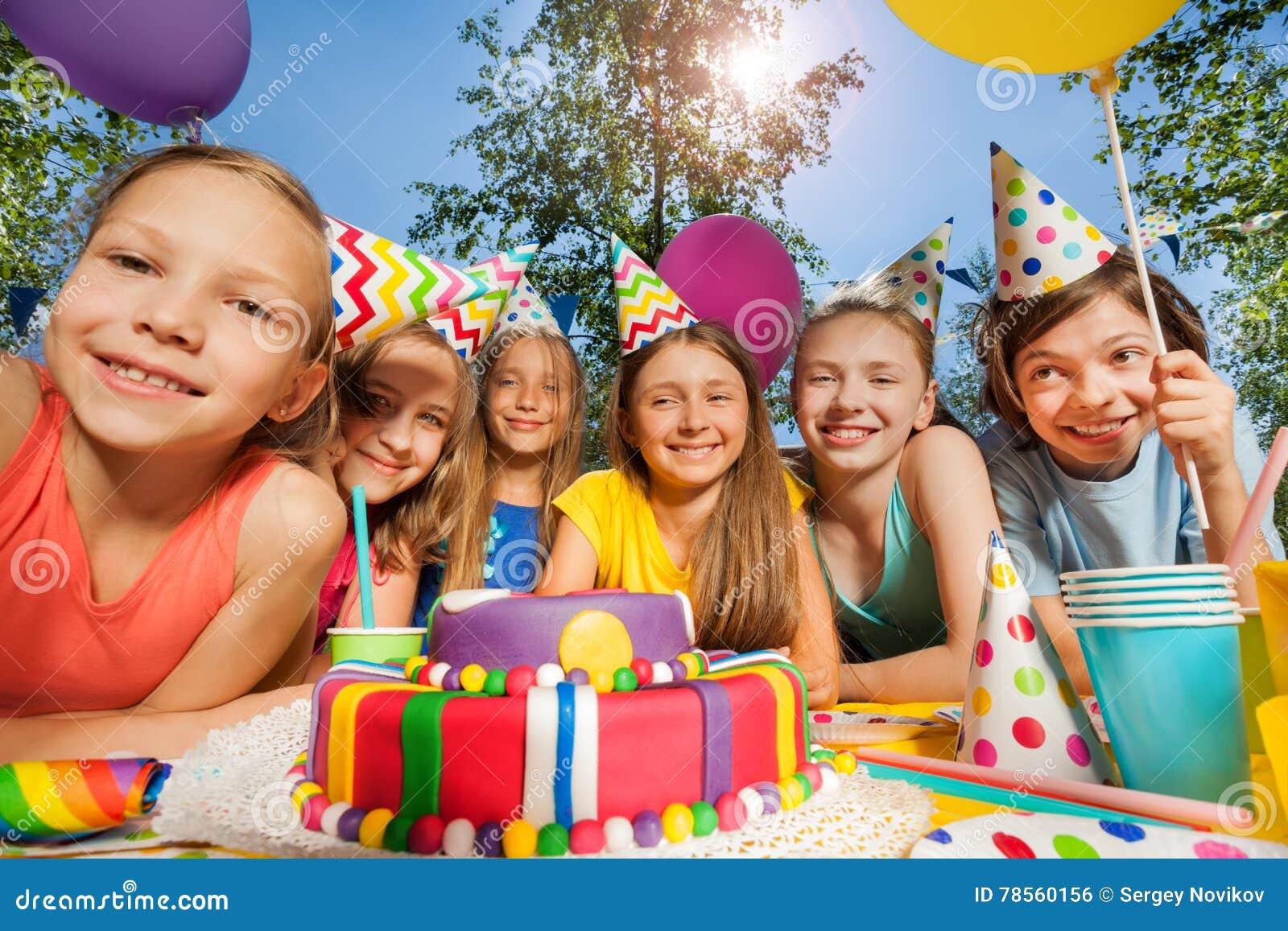 Seis niños felices en sombreros del partido alrededor de la torta de cumpleaños