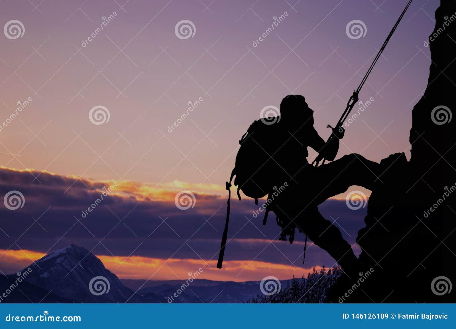 Seitenansicht über das junge mountainer Silhouettieren Sie mountainer in der Aktion