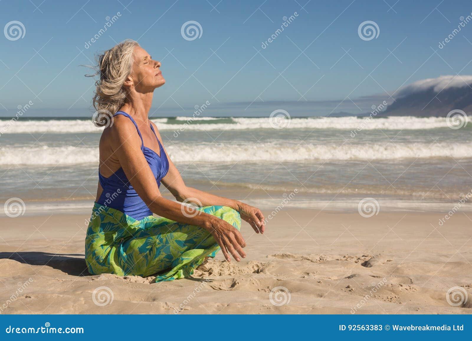 Seitenansicht der älteren Frau meditierend beim Sitzen auf Ufer