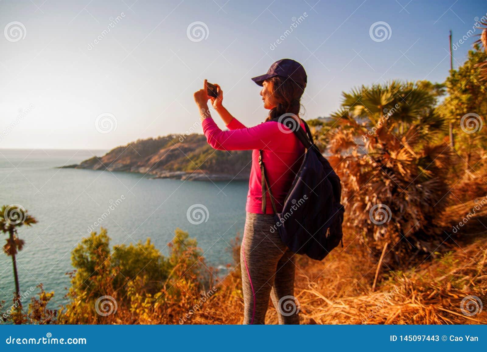 Seitenansicht der Frau mit dem Rucksack und Smartphone, die Foto in Meer auf Hügel gegen Himmel machen