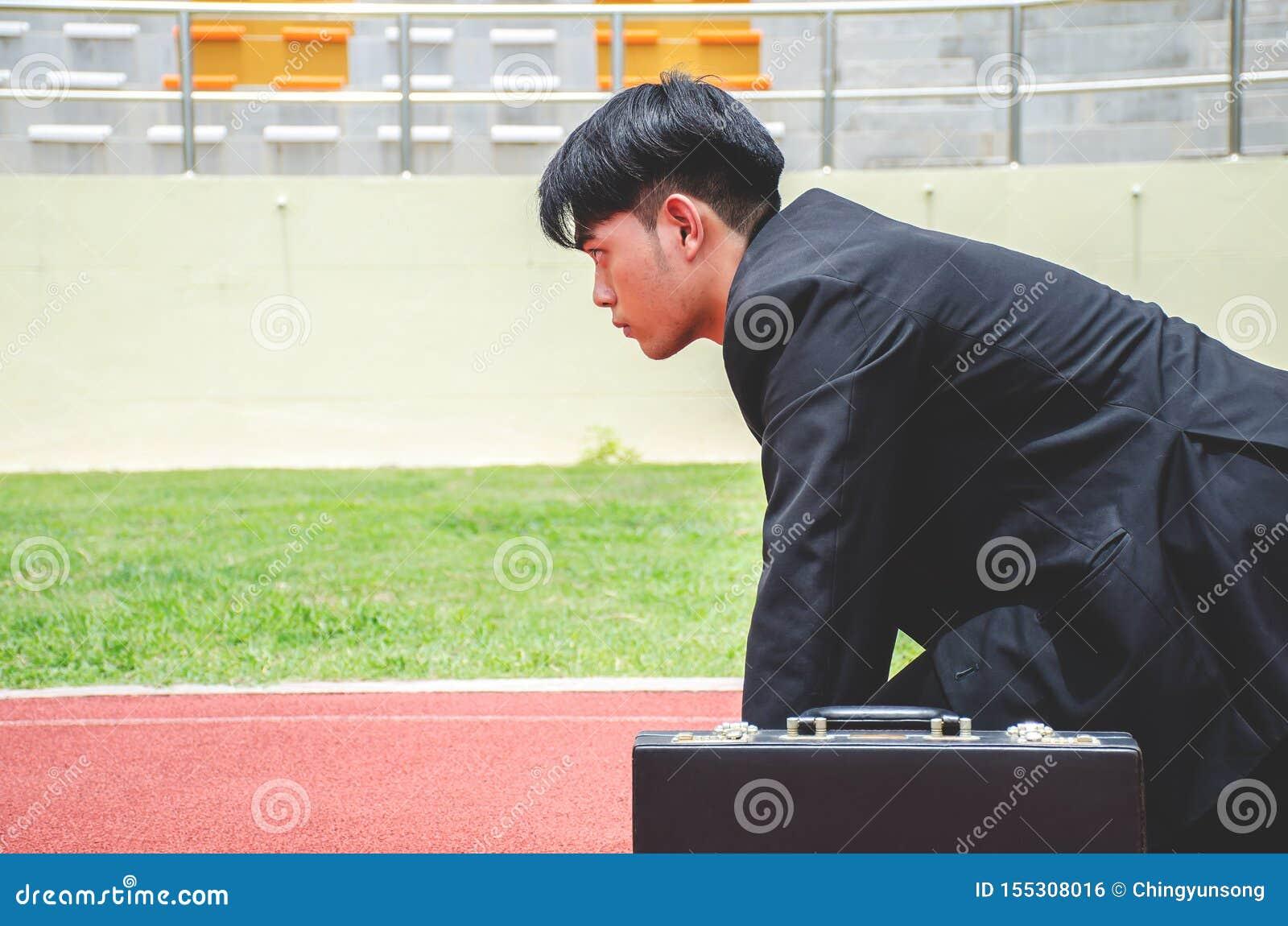 Seitenansicht des asiatischen Geschäftsmannes bereit, auf den Wegen einer Bahn zu laufen