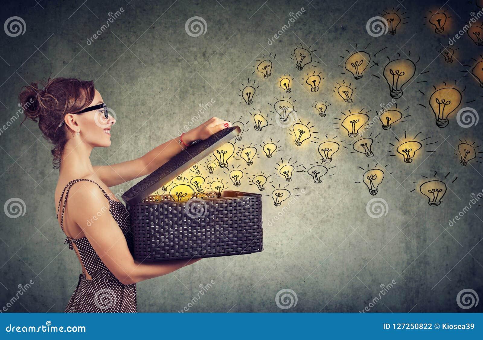 Seitenansicht einer Frau mit dem Kasten voll von den glänzenden Ideen, die kreativ sind