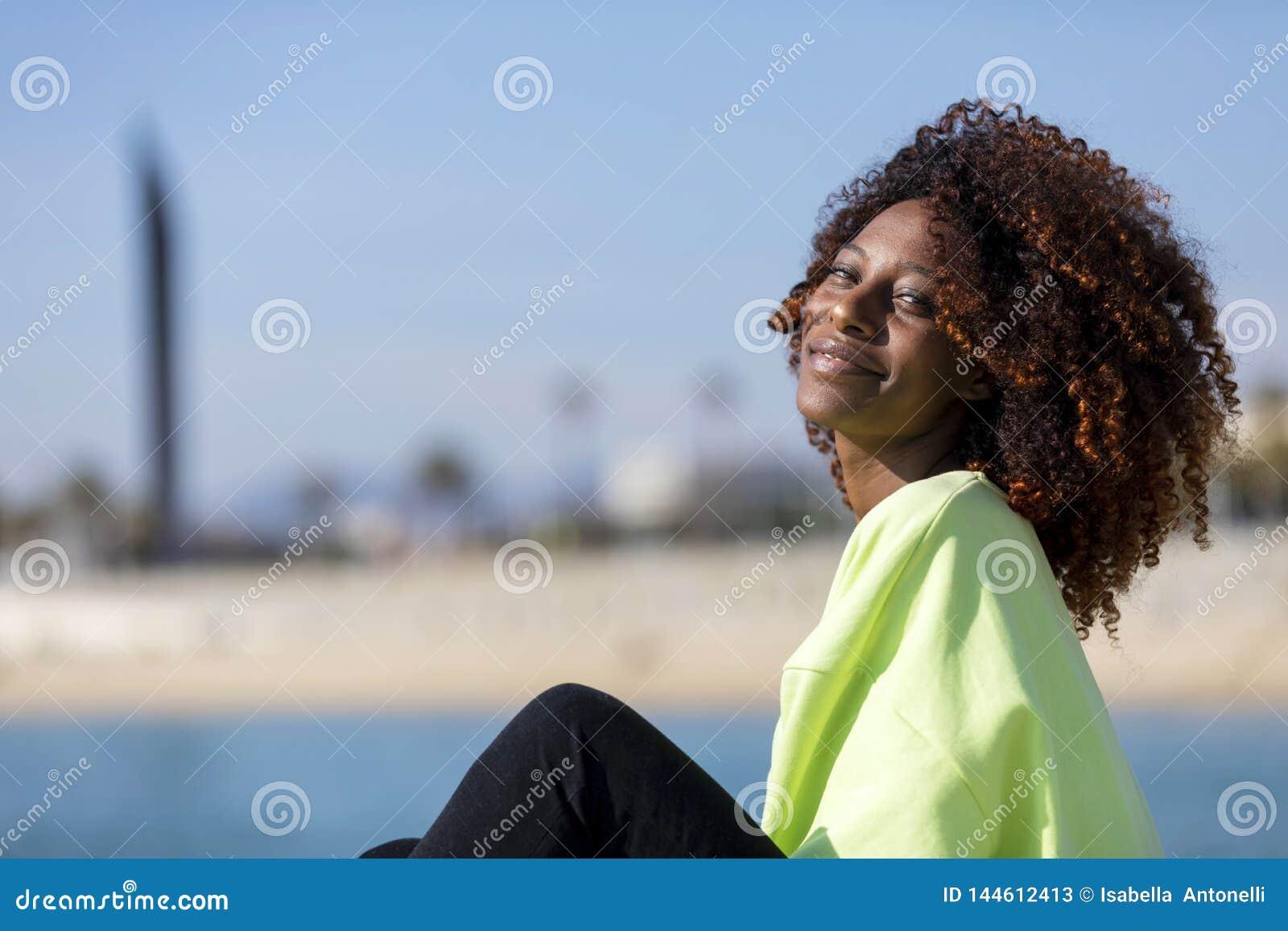 Seitenansicht einer sch?nen gelockten Afrofrau, die auf den lachenden Wellenbrecherfelsen beim Kamera drau?en schauen sitzt