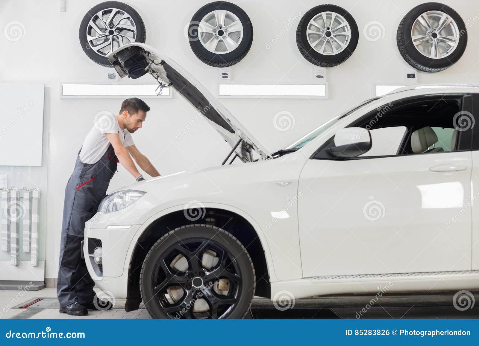 Seitenansicht in voller Länge des Untersuchungsautomotors des männlichen Mechanikers in der Reparaturwerkstatt