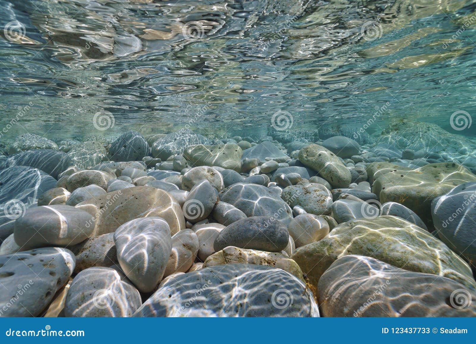 Seixos e rochas subaquáticos abaixo da superfície da água