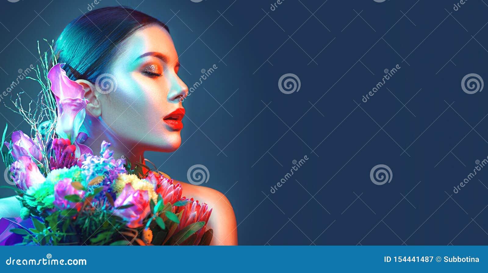 Seksowna brunetka modela dziewczyna z bukietem piękni kwiaty Piękno młoda kobieta z wiązką kwiaty w kolorowych neonowych światłac
