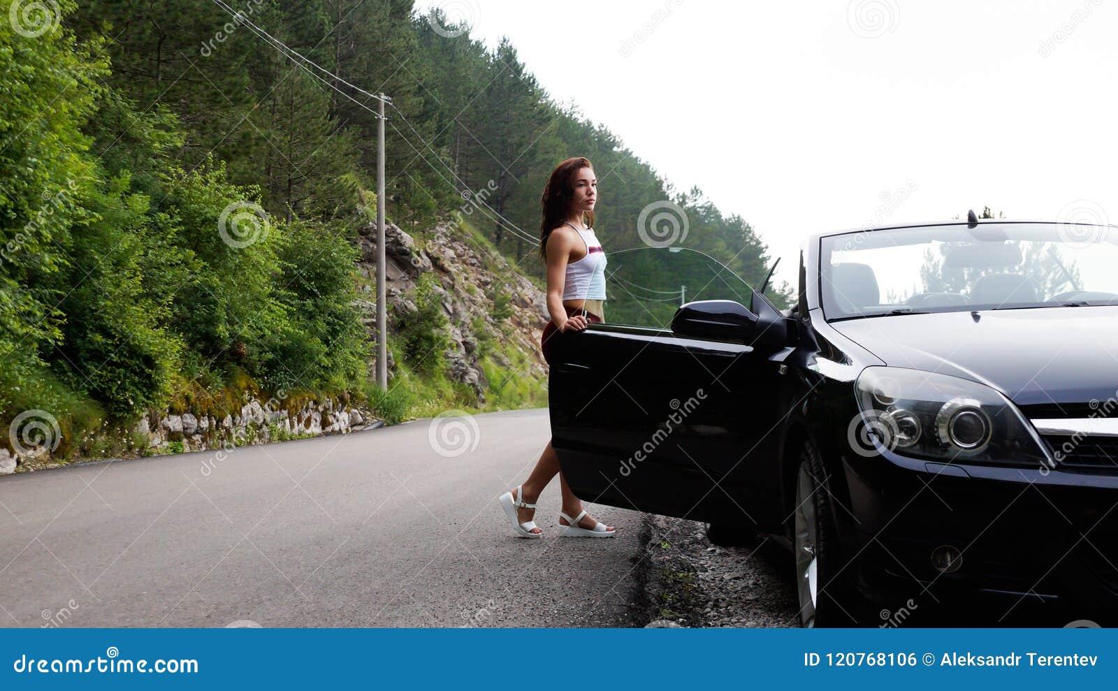 Seksowna brunetka trzyma otwarte drzwi czarny kabriolet Ubierający w krótkich czerwonych skrótach i białej koszulce