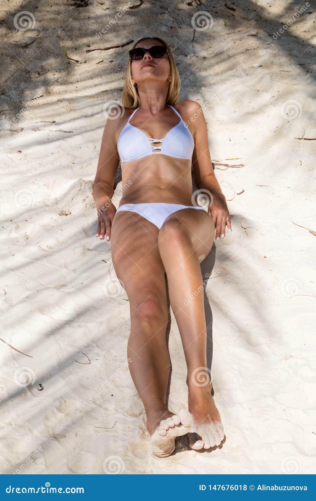 Seksowna garbnikuj?ca dziewczyna w bia?ym swimsuit pozuje na piaskowatej pla?y Pi?kny model sunbathes i odpoczywa na oceanu brzeg