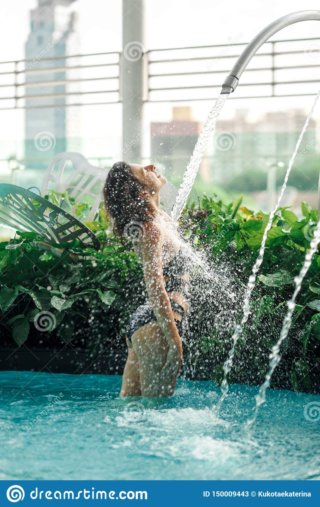 Seksowna szczup?a kobieta w swimsuit wp8lywy bra? pryszni? w basenie mi?dzy zielonymi krzakami na dachu z miasto g??bika t?em