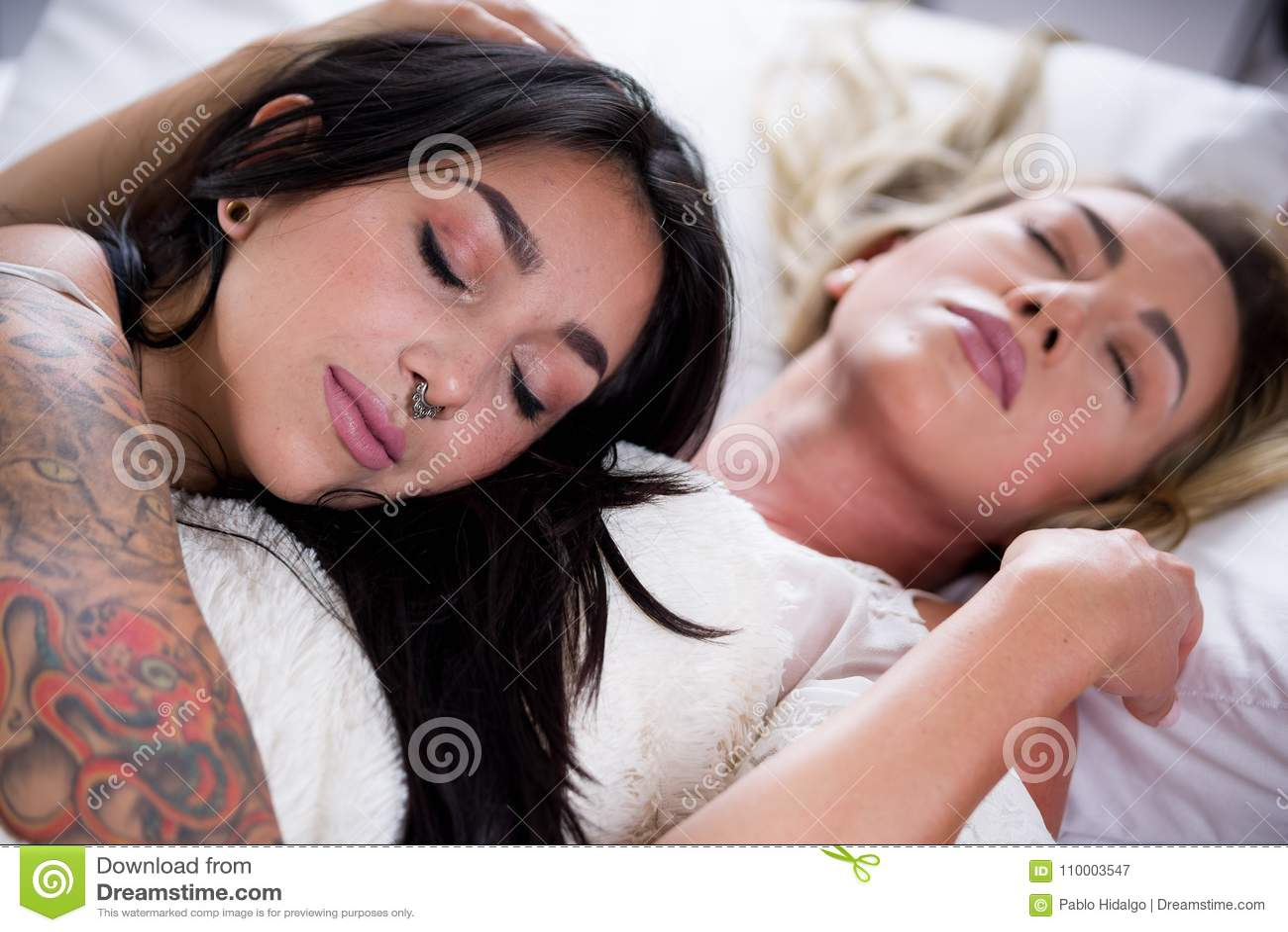 Seksowni lesbians kochankowie w łóżku przy rankiem, brunetki dziewczyna śpią nad blondynki dziewczyny klatką piersiową w białym t