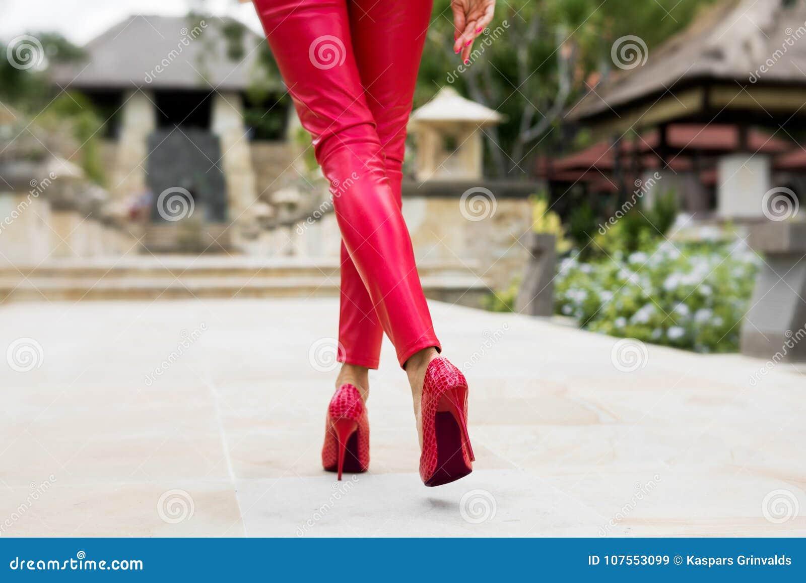 Seksowny kobiety odprowadzenie w czerwieni spodniach i czerwonych piętach
