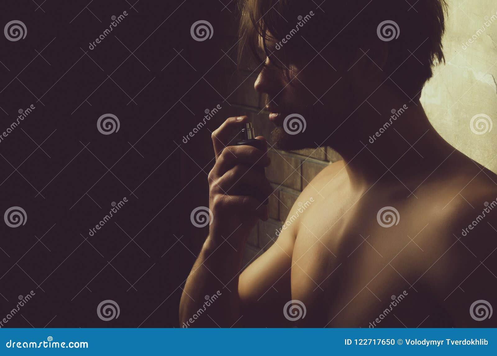 Seksowny mężczyzna wącha pachnidło aromat z nagą klatką piersiową