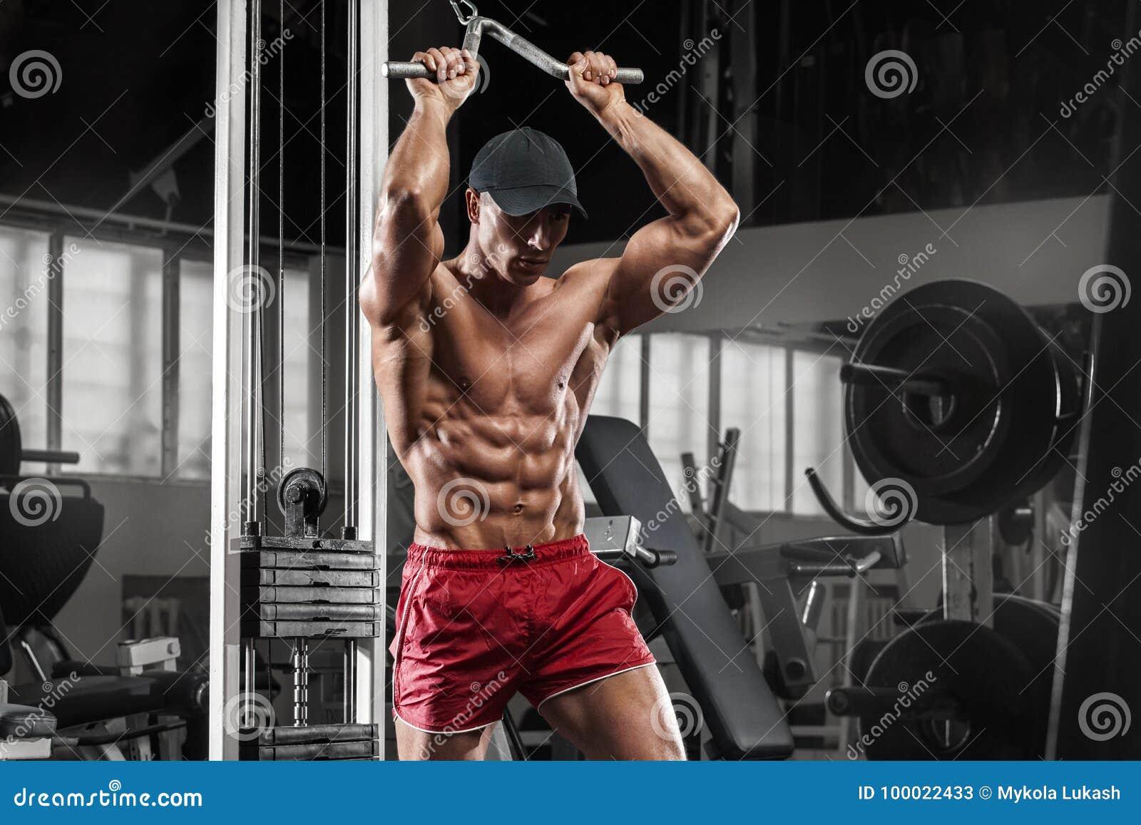 Seksowny mięśniowy mężczyzna pracujący w gym robi ćwiczeniom out, silny męski nagi półpostaci abs