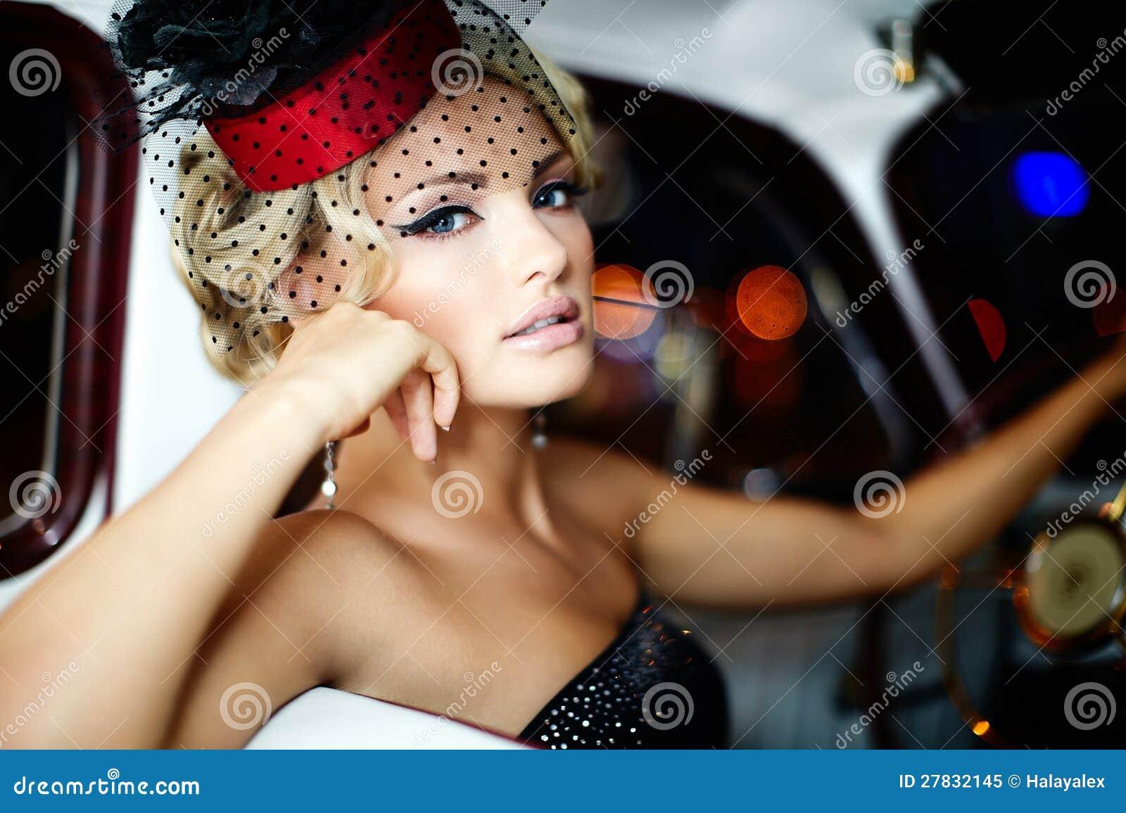 Seksowny mody dziewczyny obsiadanie w starym samochodzie