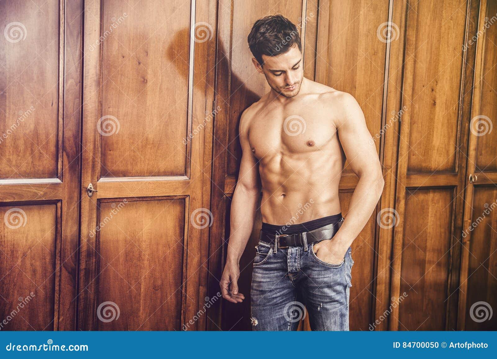 Seksowny przystojny młodego człowieka stać bez koszuli przeciw garderobie