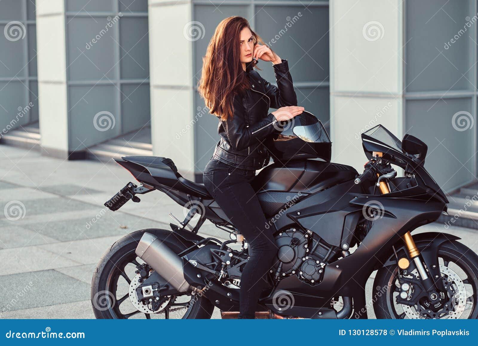 Seksowny rowerzysta dziewczyny obsiadanie na jej superbike na zewnątrz budynku
