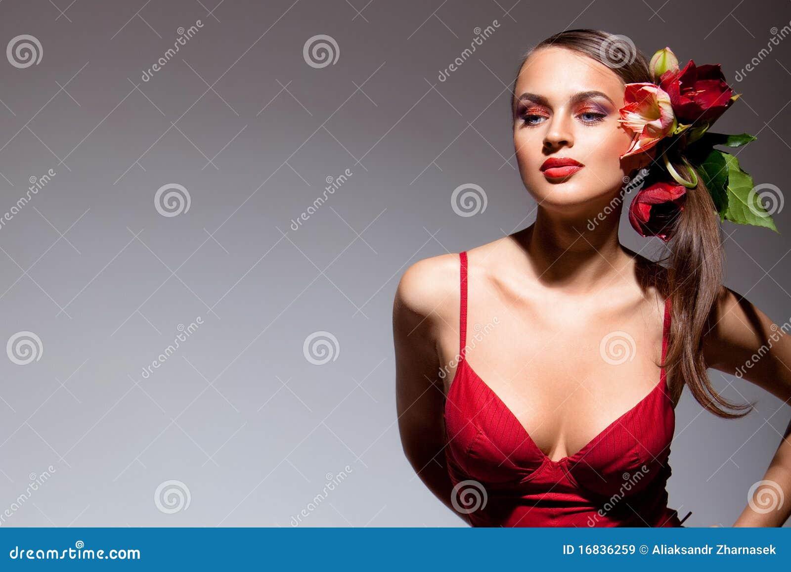 Seksueel meisje in rode kleding met bloemen in haar haar