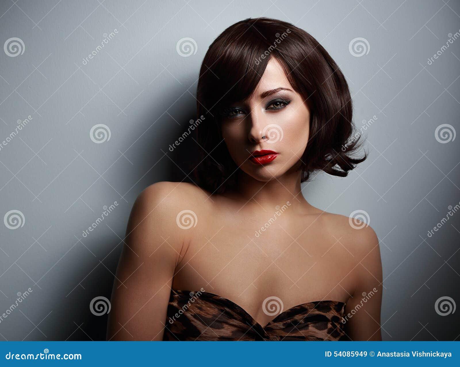 Seksuele vrouw die met zwart kort haar op donkere achtergrond kijken