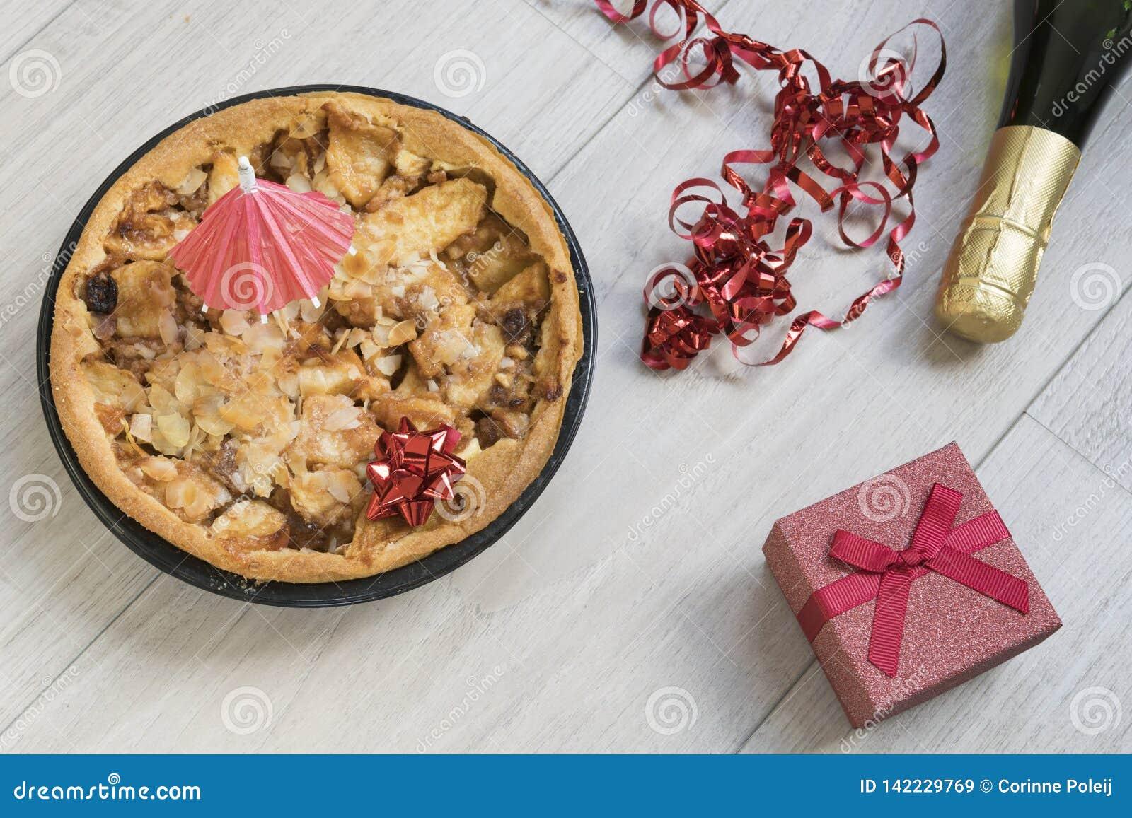 Selbst gemachter Apfelkuchen mit rotem Geschenk und Alkohol