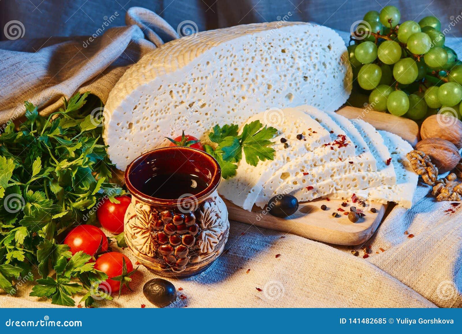 Selbst gemachter georgischer Imeretian-Käse auf einem hölzernen Brett, Kirschtomaten, Walnüsse, Trauben, Gewürze