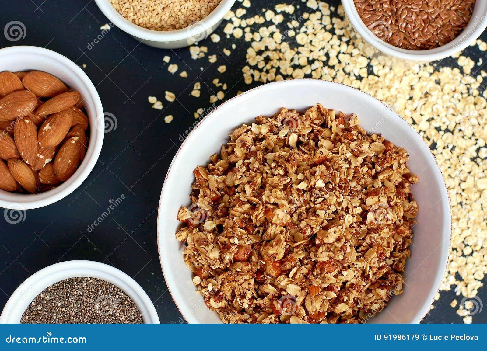 Selbst gemachtes Granola in der weißen Schüssel mit Mandel und Samen auf schwarzem Hintergrund