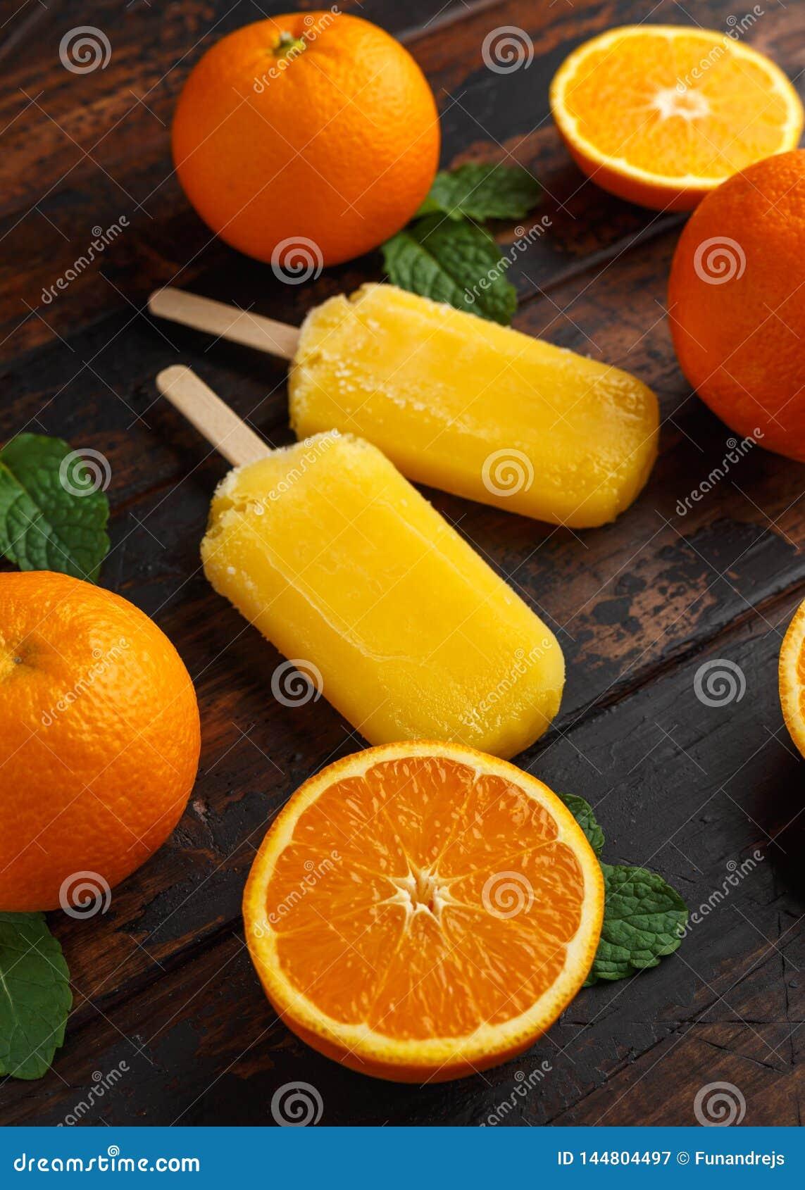 Selbst gemachtes orange Eis am Stiel, Eislutscher, auf Holztisch Sommerlebensmittel