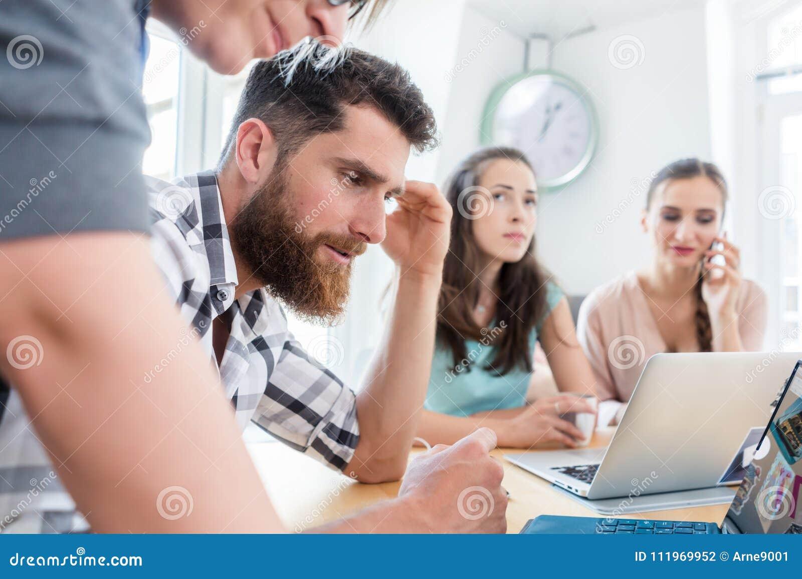 Selbstständiger junger Mann, der eine schwierige Aufgabe beim Arbeiten analysiert
