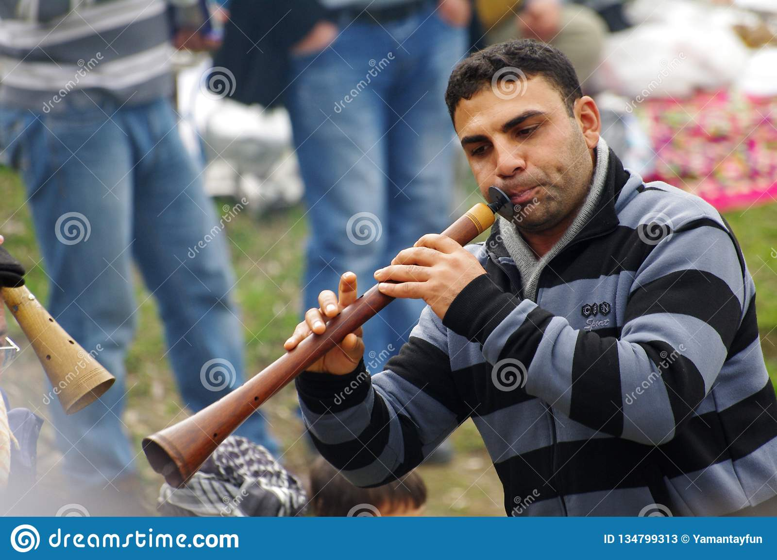 A gypsy man performing music by traditional Turkish clarion