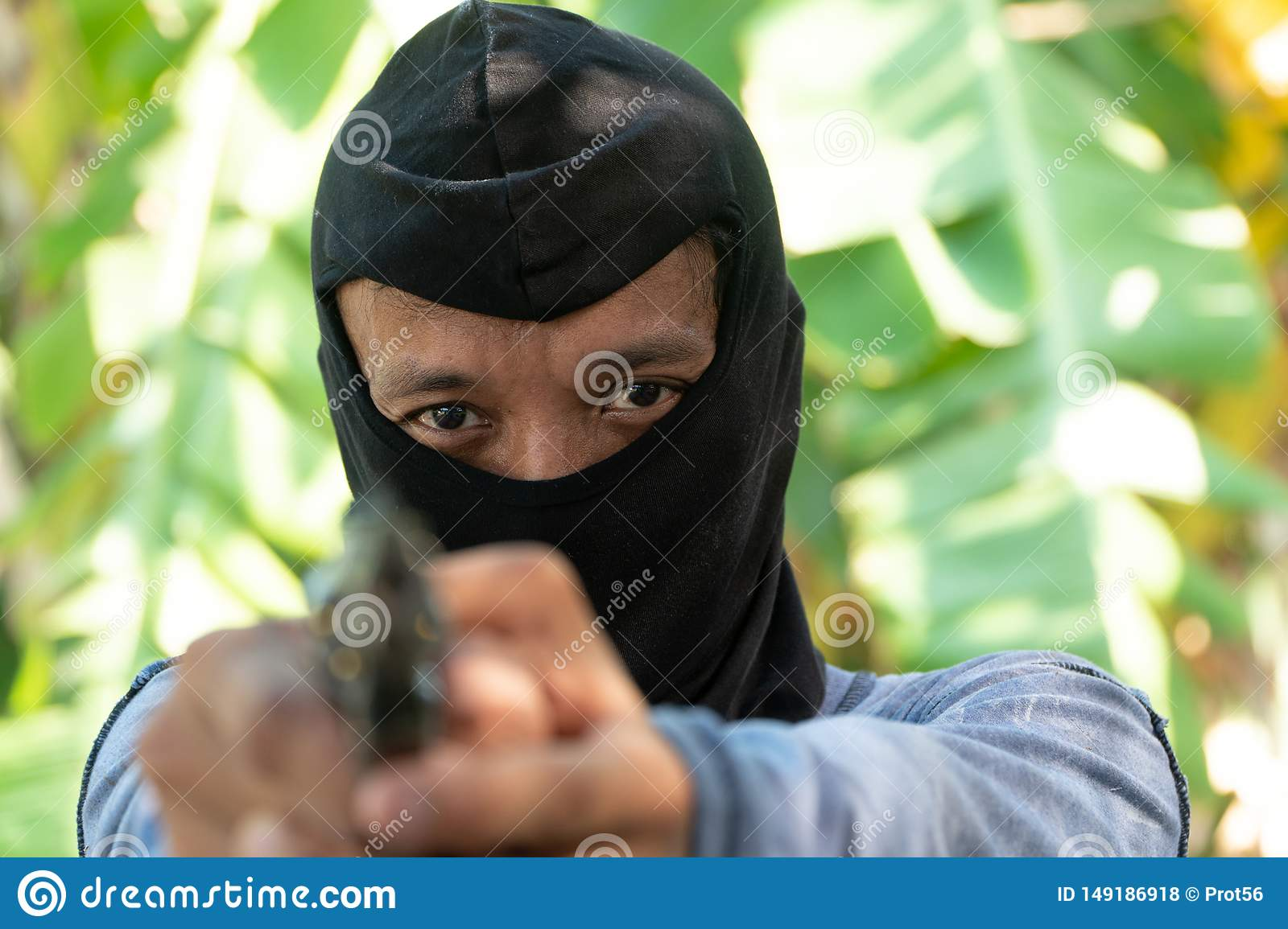 Select focus of crime eyes. Robber in black ski mask aims with gun