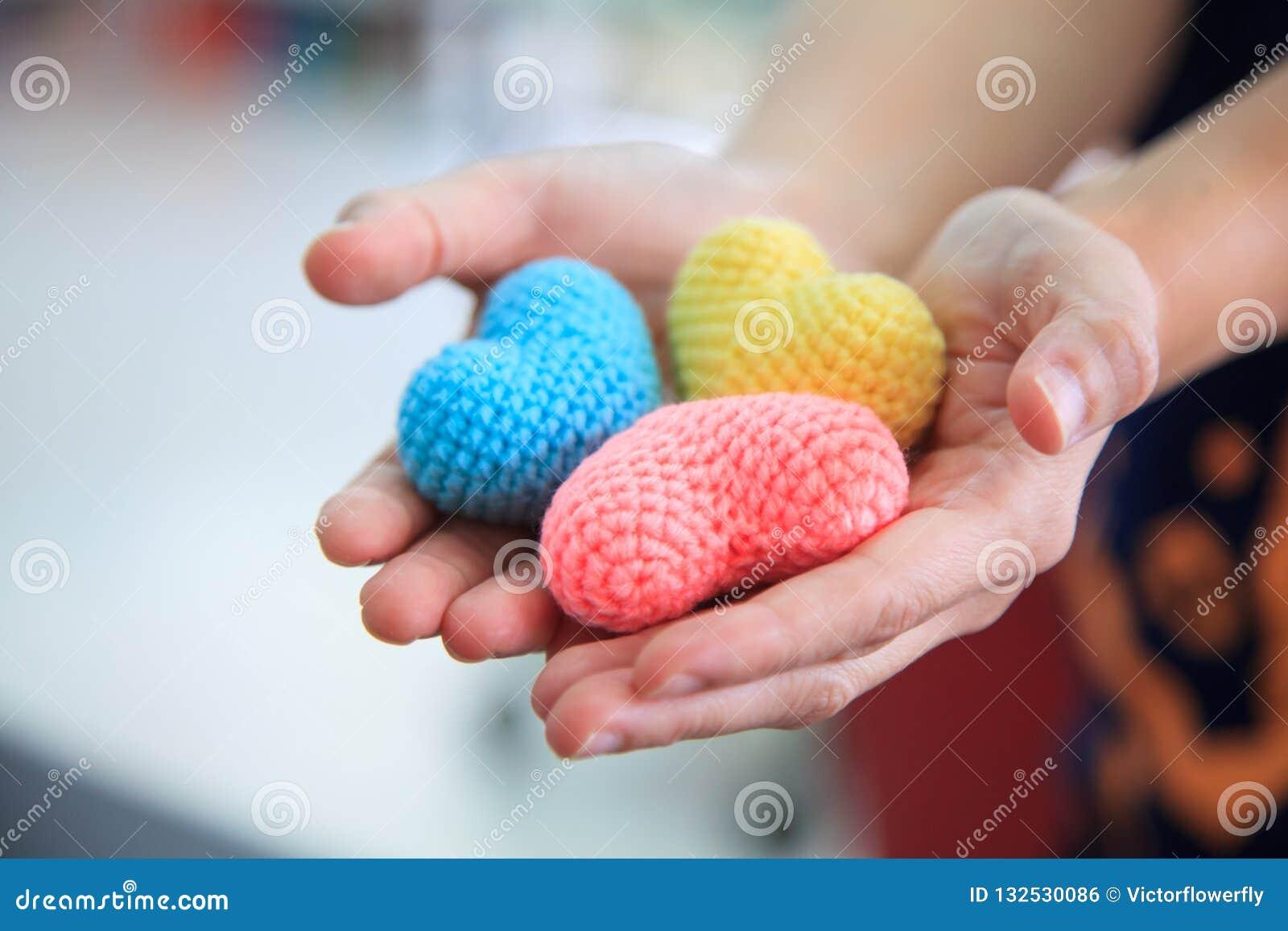 Selectieve nadruk kleurrijke veelkleurige breiende die harten door beide handen van het wijfje worden gehouden, die helpend hande