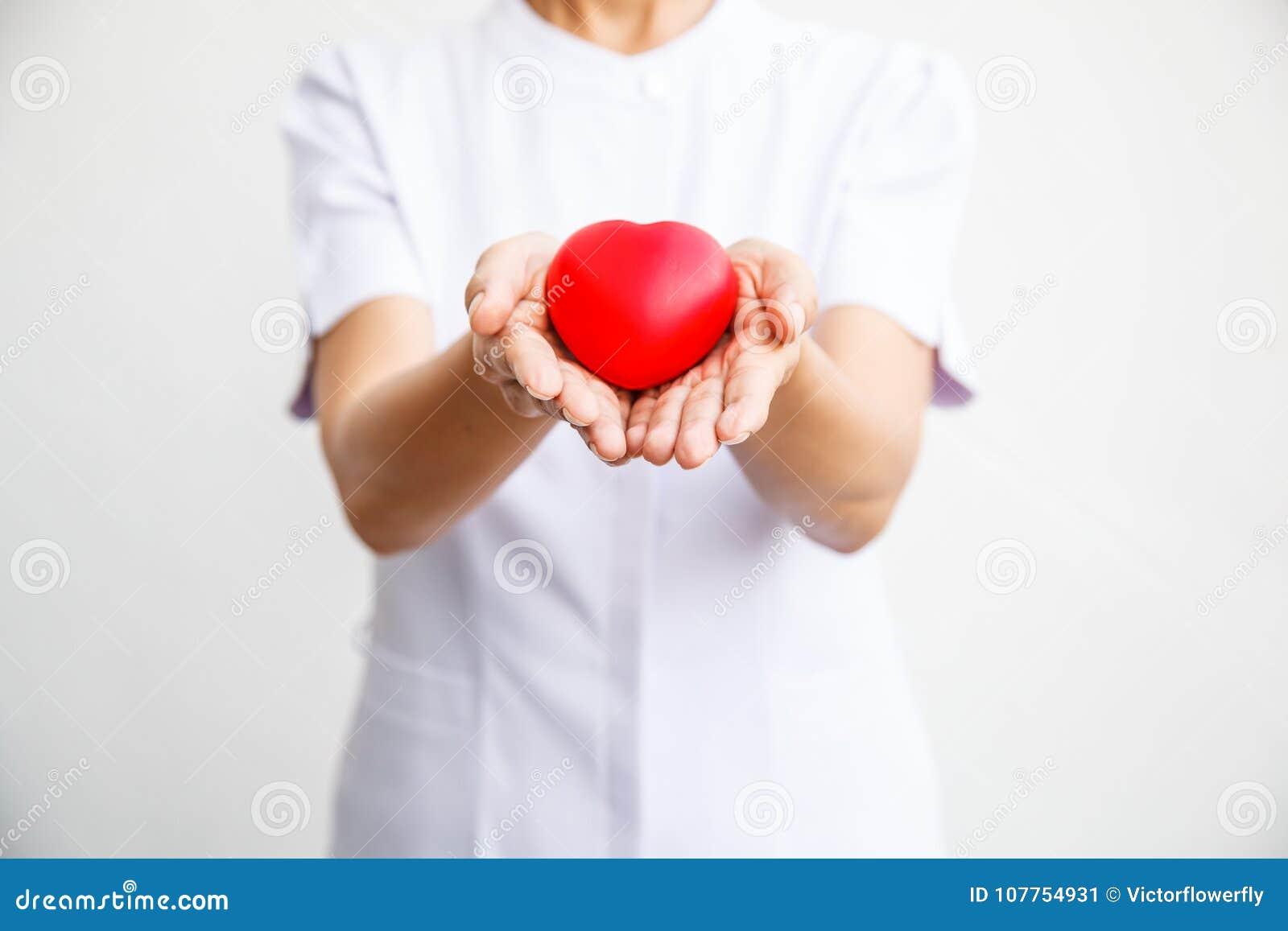 Selectieve nadruk van rood die hart door vrouwelijke verpleegster ` s beide hand wordt gehouden, die gevend al inspanning om hoog