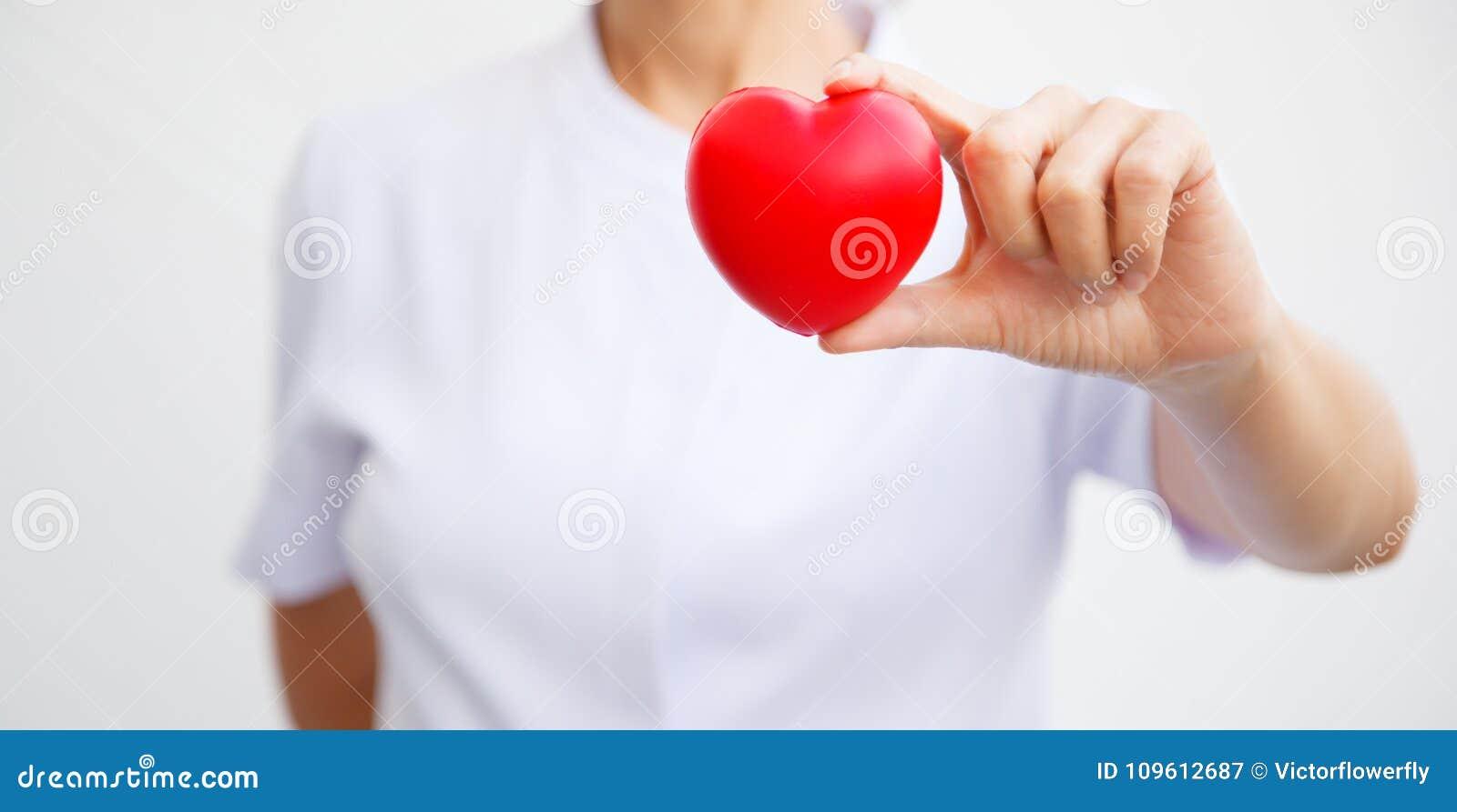 Selectieve nadruk van rood die hart door vrouwelijke verpleegsters` s hand wordt gehouden, die gevend al inspanning om hoogte te