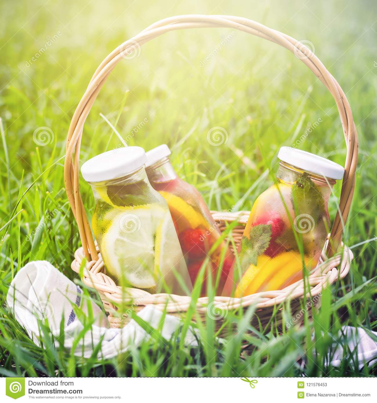 Selection of summer lemonades. Basket on the meadow with refresh