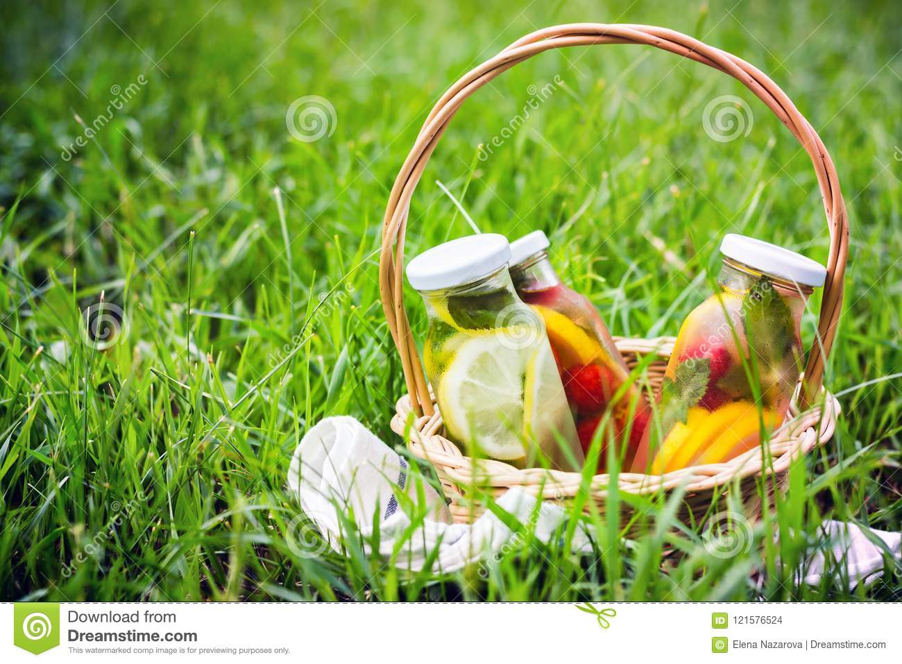 Selection of summer lemonades. Basket on the meadow with refreshing drinks