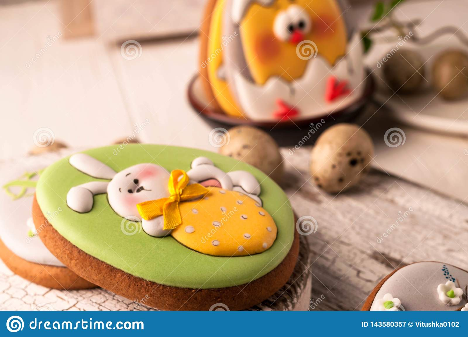 Easter green cookie with painted easter bunny in white bow holding strawberry on white cutting boards and wooden surface
