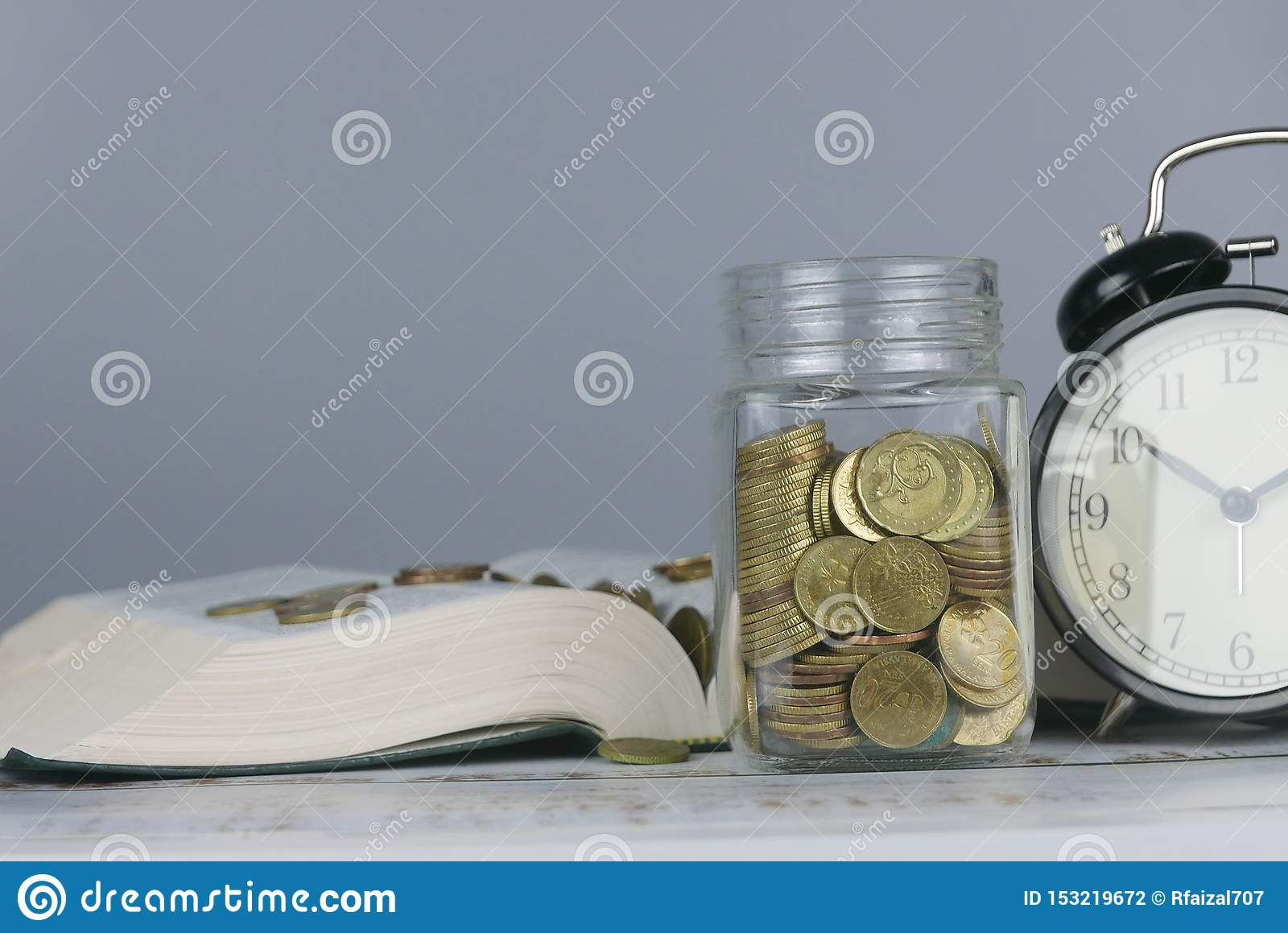 Selective focus of Gold coins on book with clock. Finance and education concept