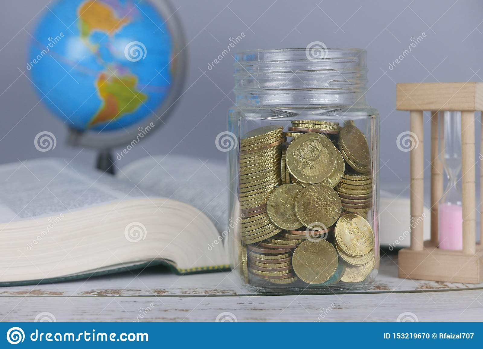 Selective focus of Gold coins, book, hourglass and globe. Finance and education concept