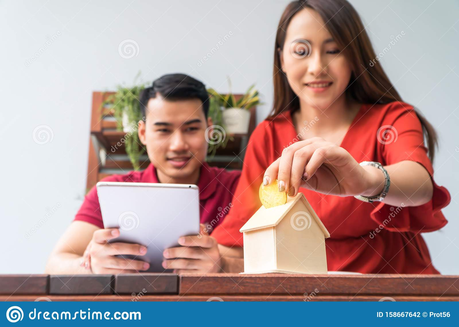 Selective focus of golden coin. Happy Asian couples smiling Because it is profitable from investment And have savings for buying a