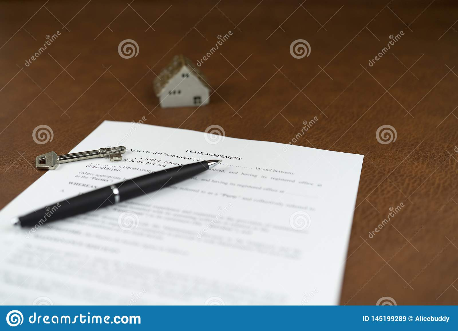 Selective focus of lease agreement with ceramic home and pen