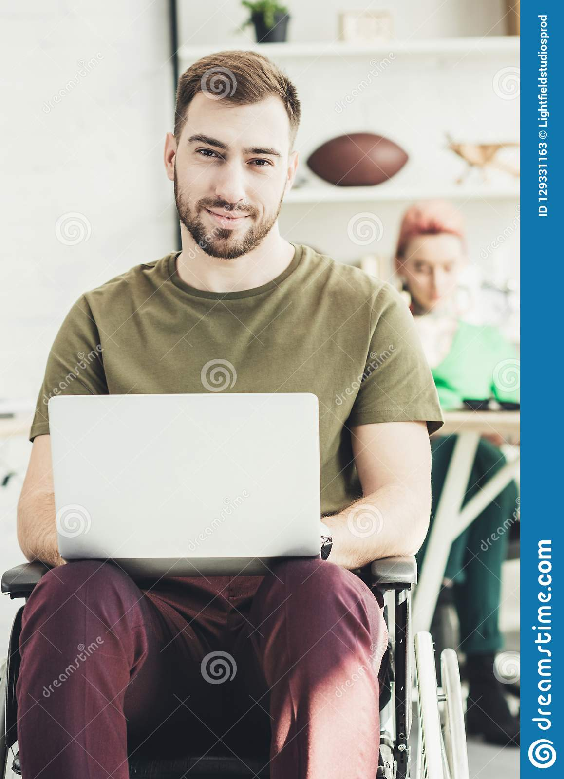 Selective focus of smiling disabled man with laptop and colleague behind in office stock photos