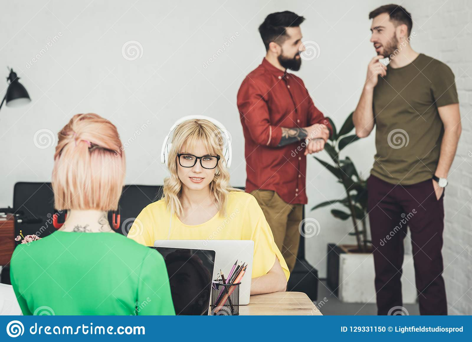 Selective focus of young blogger in headphones and colleagues talking behind in office stock photo