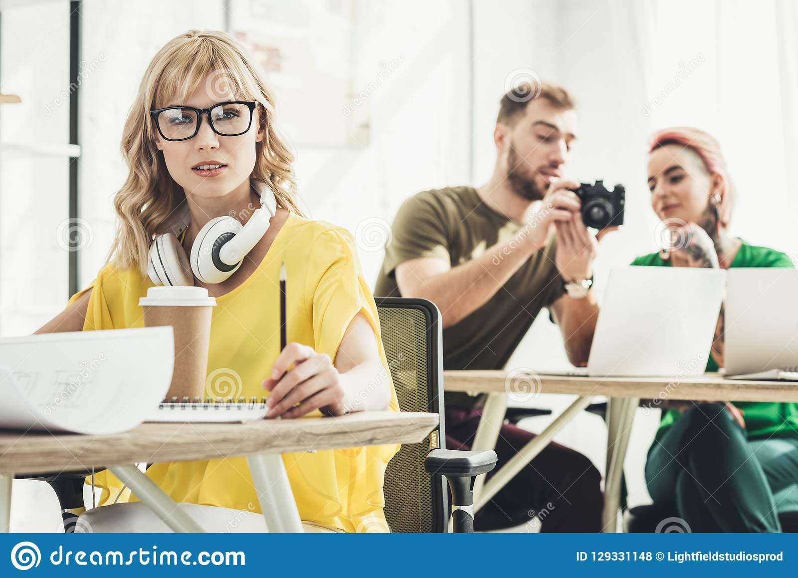 Selective focus of young blogger with headphones looking at camera and colleagues working behind in office royalty free stock photos