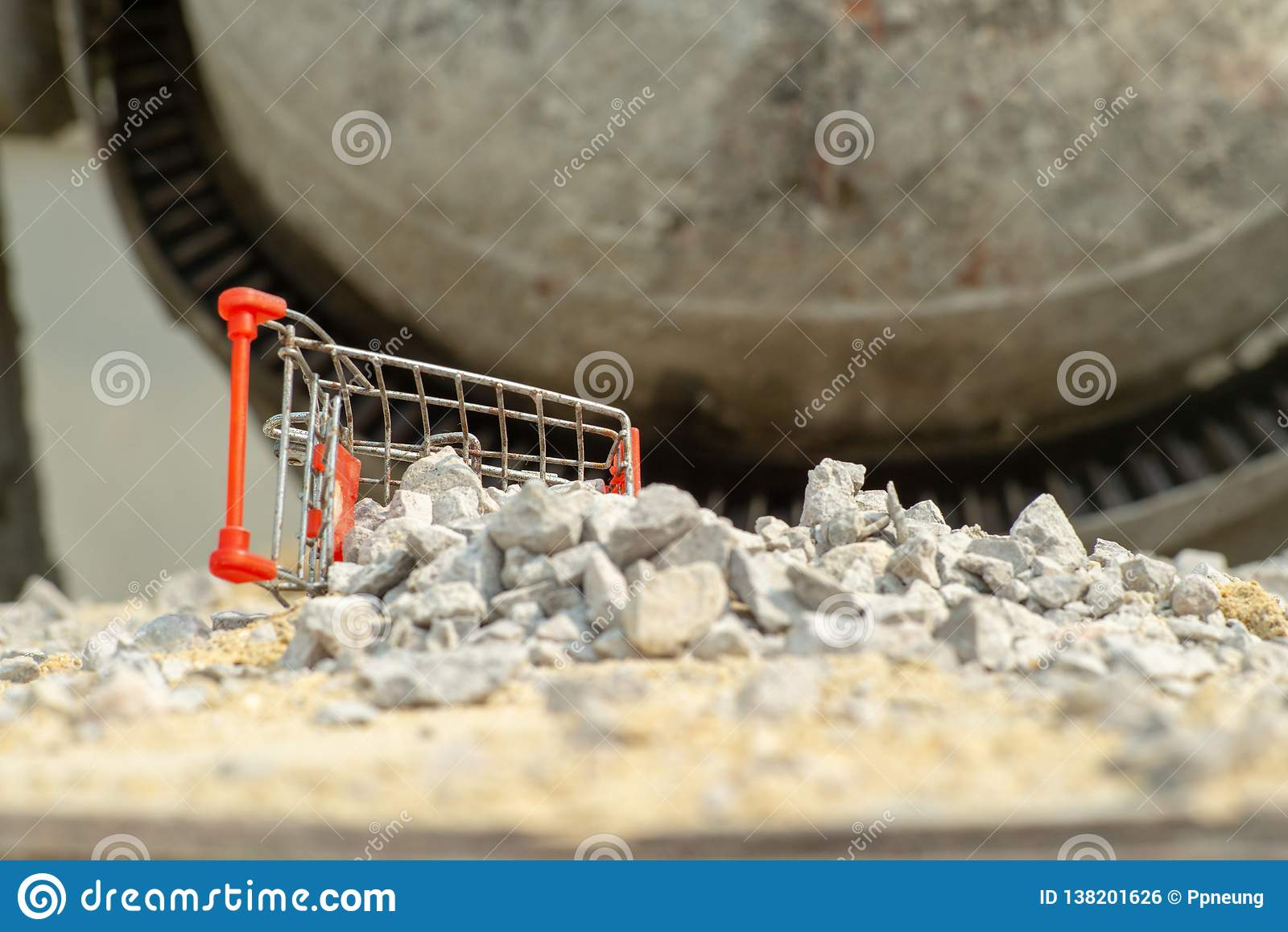 Selective focus on shopping trolley falling on the pile of crushed stone at the construction site