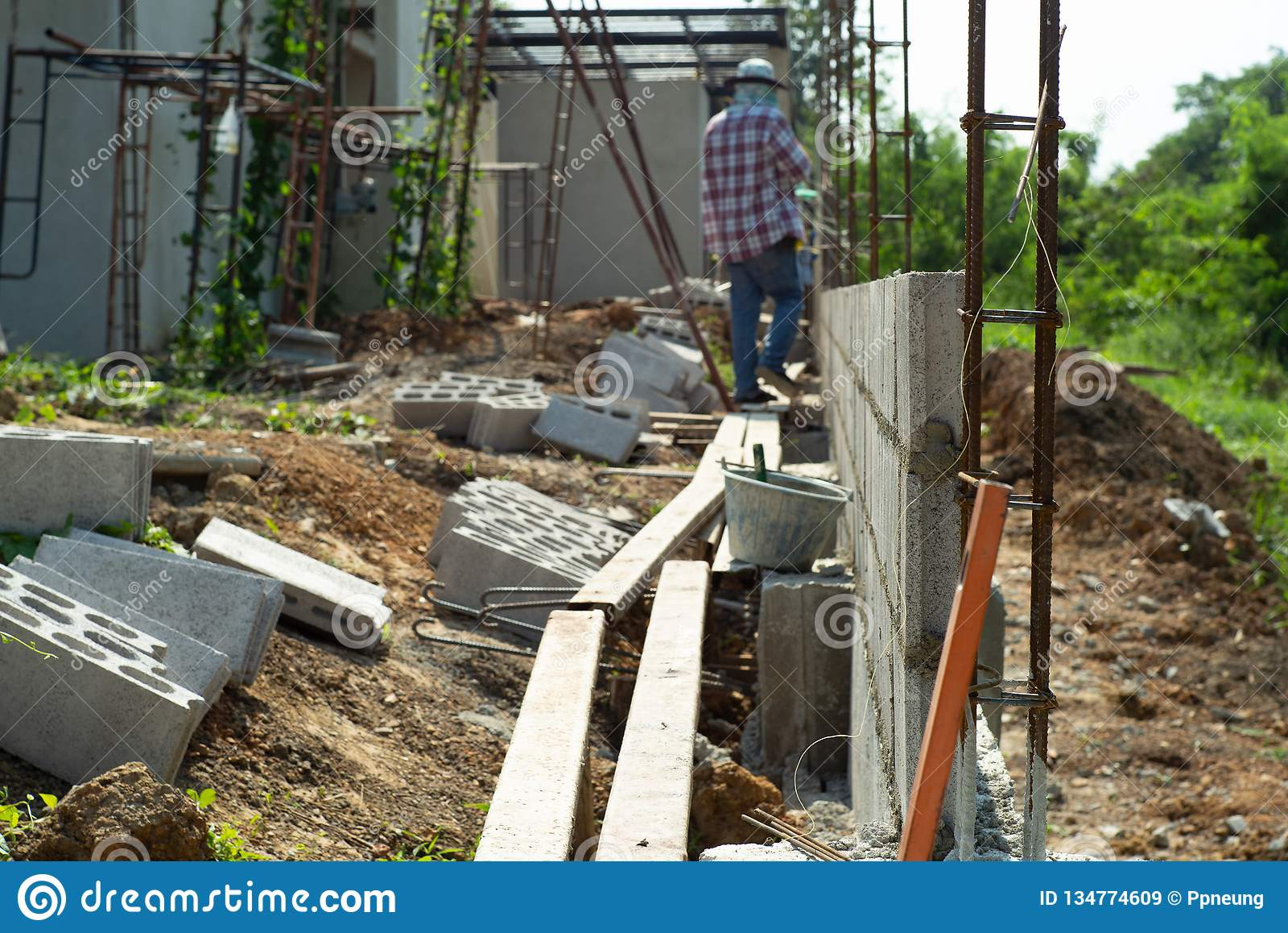 Selekcyjna ostrość wzmacnienie stalowa i cementowa cegły ściana z zamazanymi pracownikami w tle przy budową