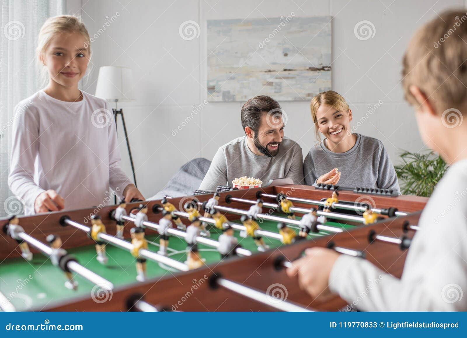 Selektiv fokus av att le familjen som tillsammans spelar tabellfotboll