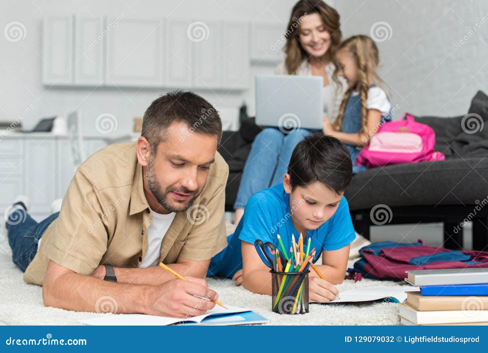 Selektiv fokus av fadern och sonen som tillsammans gör läxa medan moder och dotter som använder bärbara datorn på soffan